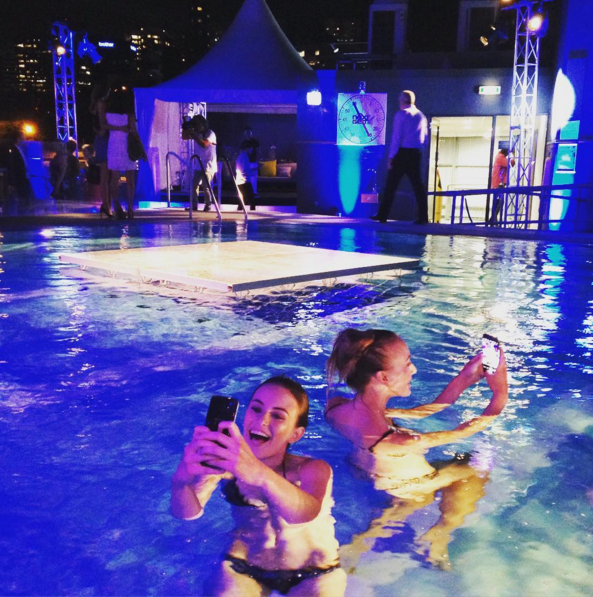 Models in swimsuits using the waterproof GS7 Samsung at tonight's Remix rooftop pool party at Next Gen.