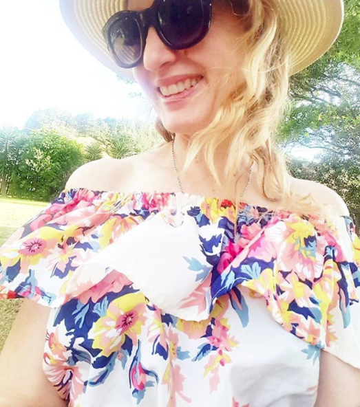In Coromandel in an off the shoulder floral dress I bought secondhand. Straw hat by Max, eyewear by Le Specs.